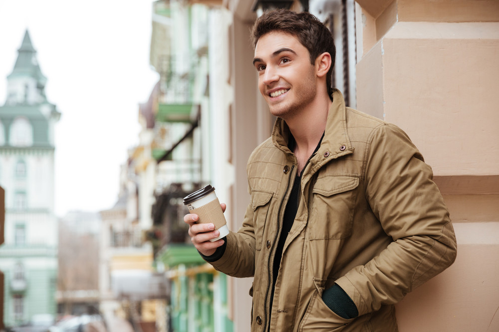 Image of cheerful young man walking on the street and looking aside while holding cup of coffee.