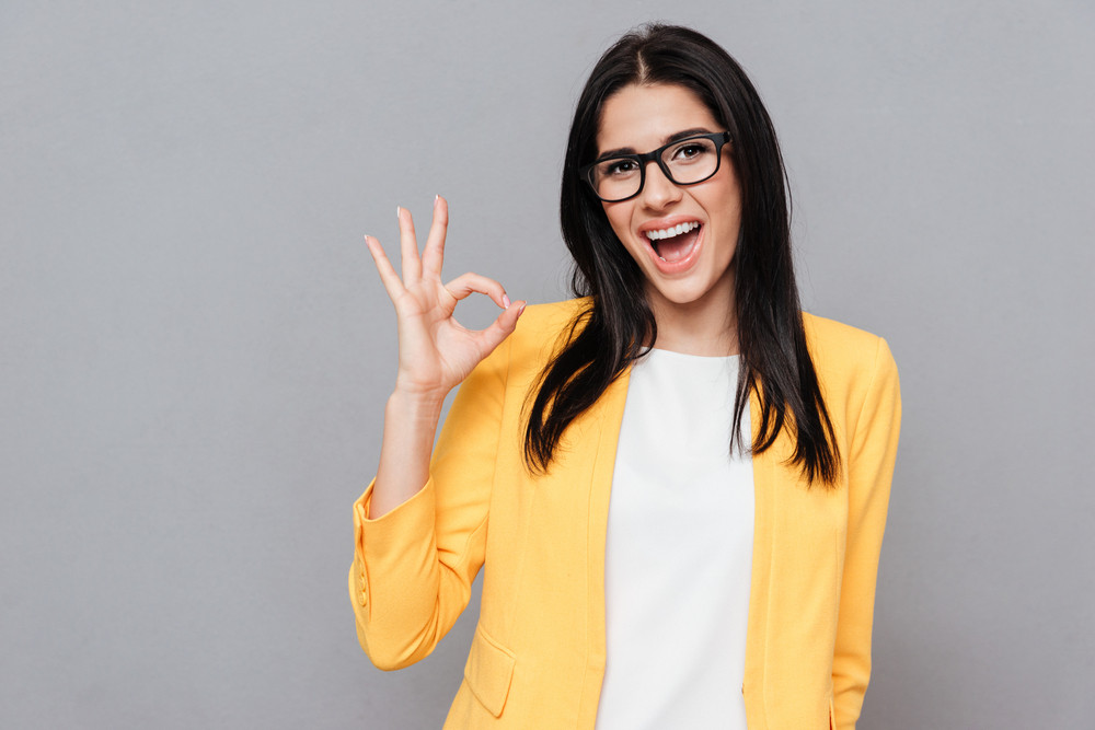 Image of cheerful young woman wearing eyeglasses and dressed in yellow jacket make Okay gesture over grey background. Look at camera.