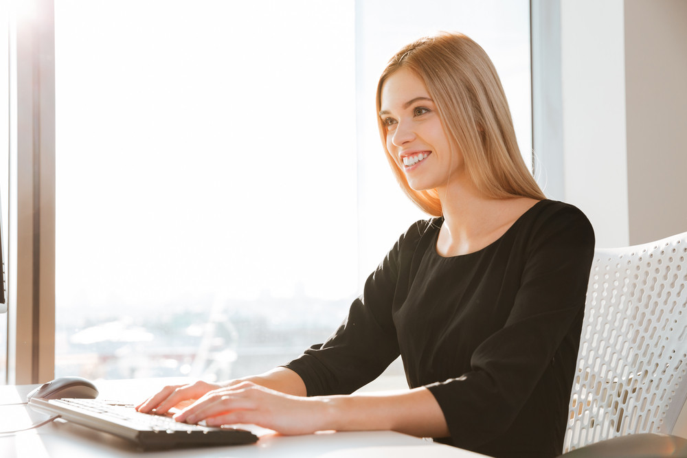 Image of cheerful young woman worker using computer in office and typing by keyboard. Look at computer.