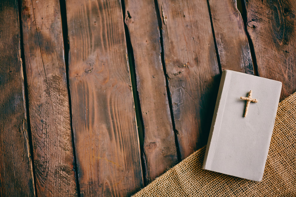 Image of Christian book with cross on its cover on wooden background