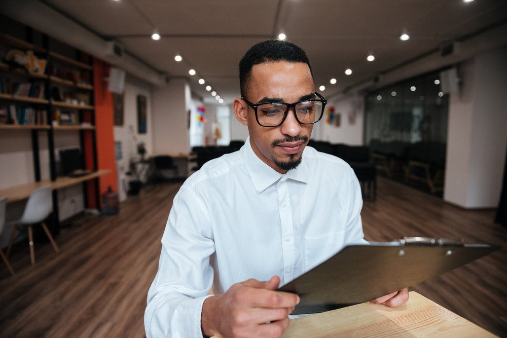 Image of concentrated african businessman wearing glasses sitting at the table and looking at notepad. Coworking.