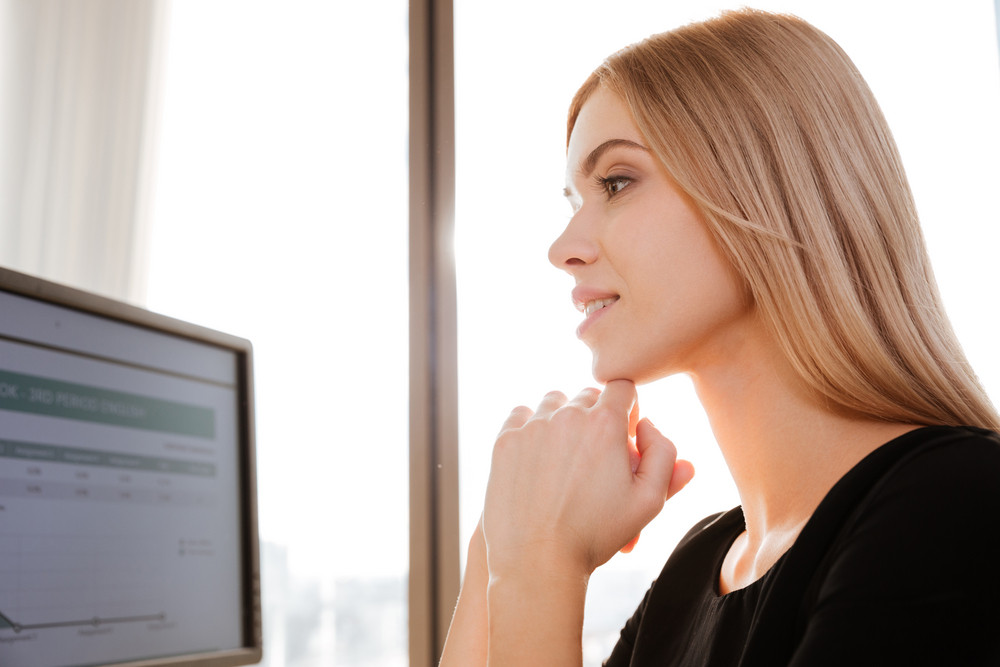 Image of concentrated young lady worker sitting in office near computer.