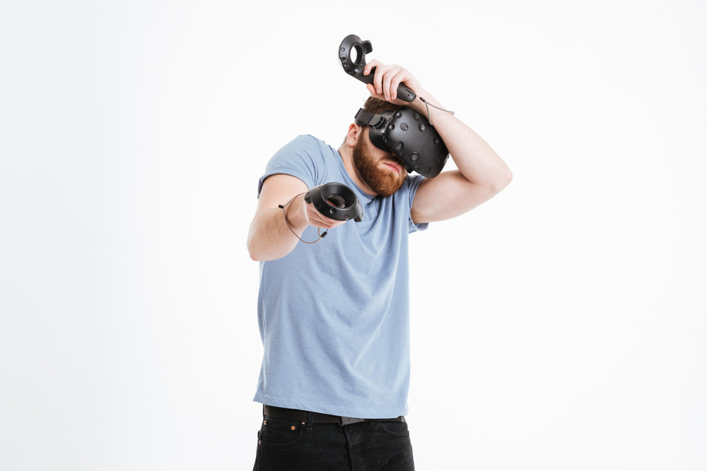 Image of confused young bearded man wearing virtual reality device standing over white background while holding joysticks in hands.