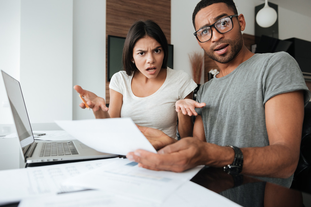 Image of confused young loving couple discussing about domestic bills at home while looking at camera and holding documents.