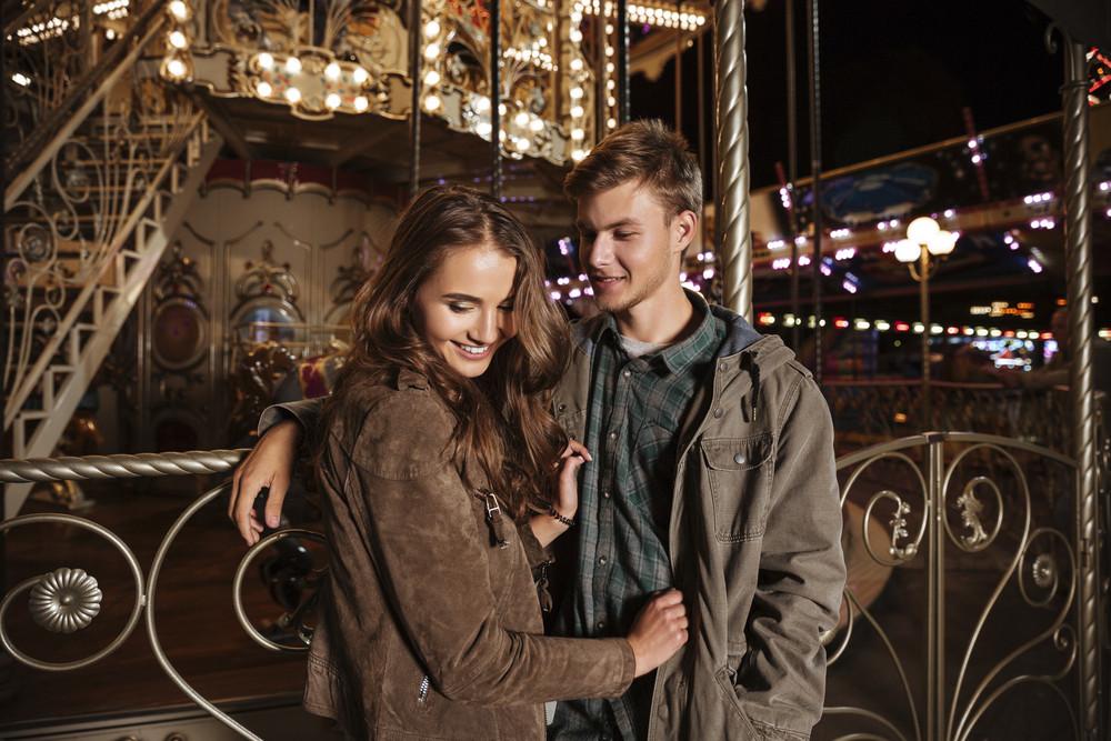 Image of couple in amusement park. hug