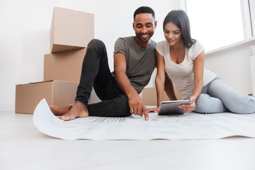 Image of couple planning decoration at new home sitting on the floor. Housewarming.
