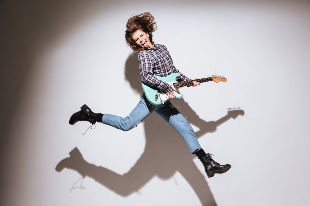 Image of emotional woman dressed in shirt in a cage holding guitar isolated over white background showing her tongue and jumping