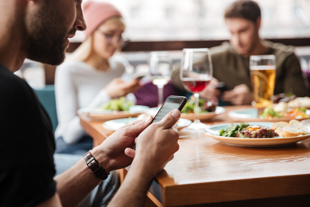 Image of friends sitting in cafe and drinking alcohol while using mobile phones. Focus on phone.