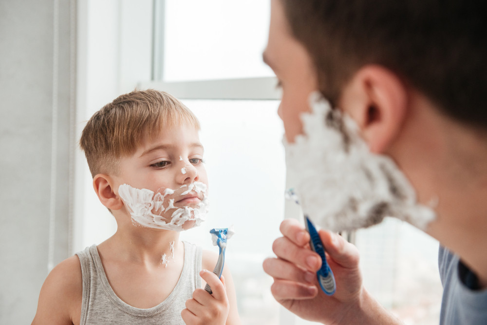 Image of funny father and son are applying shaving foam on their faces and smiling while shaving in bathroom