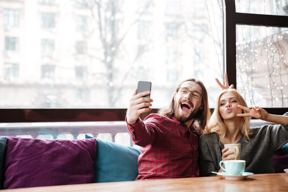 Image of funny loving couple sitting in cafe and talking while drinking coffee and make a selfie.