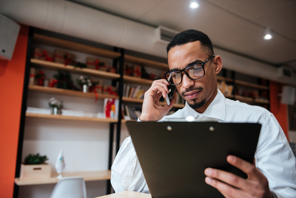 Image of handsome african businessman wearing glasses sitting at the table holding notepad talking by phone. Coworking.