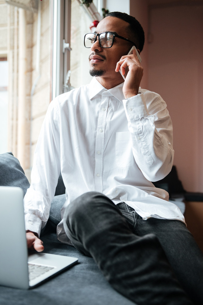 Image of handsome african businessman wearing glasses sitting near window and typing by laptop computer while talking by phone. Coworking.