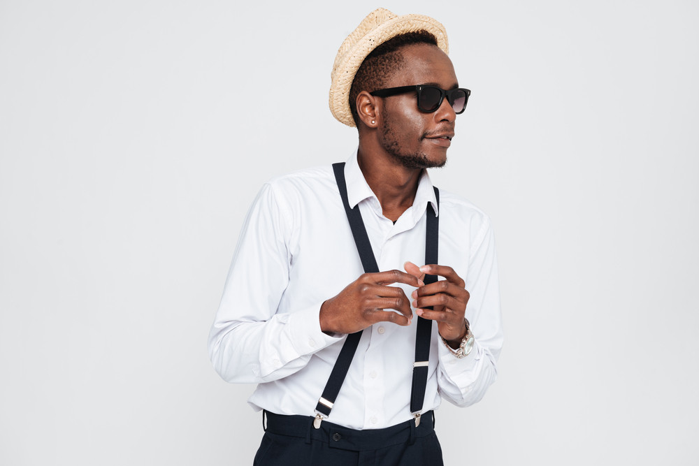 Image of handsome african man wearing hat posing in studio. Isolated over white background. Look aside.
