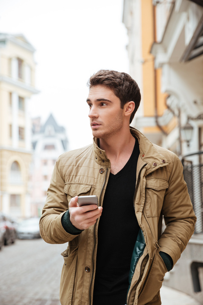 Image of handsome guy walking on street and chatting by his telephone outdoors. Look aside.