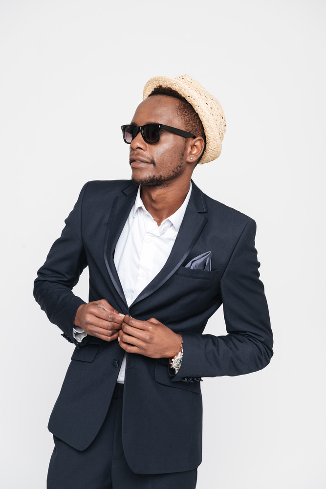 Image of handsome young african businessman wearing hat posing in studio. Isolated over white background. Look aside.