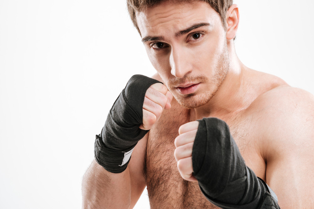 Image of handsome young man boxer standing over white background. Look at camera.