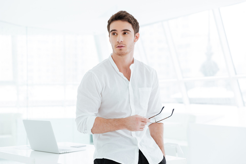 Image of handsome young man holding eyeglasses and dressed in white shirt look aside.