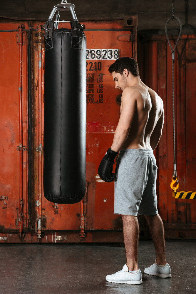 Image of handsome young strong boxer training in a gym. Looking aside. Standing near punchbag.