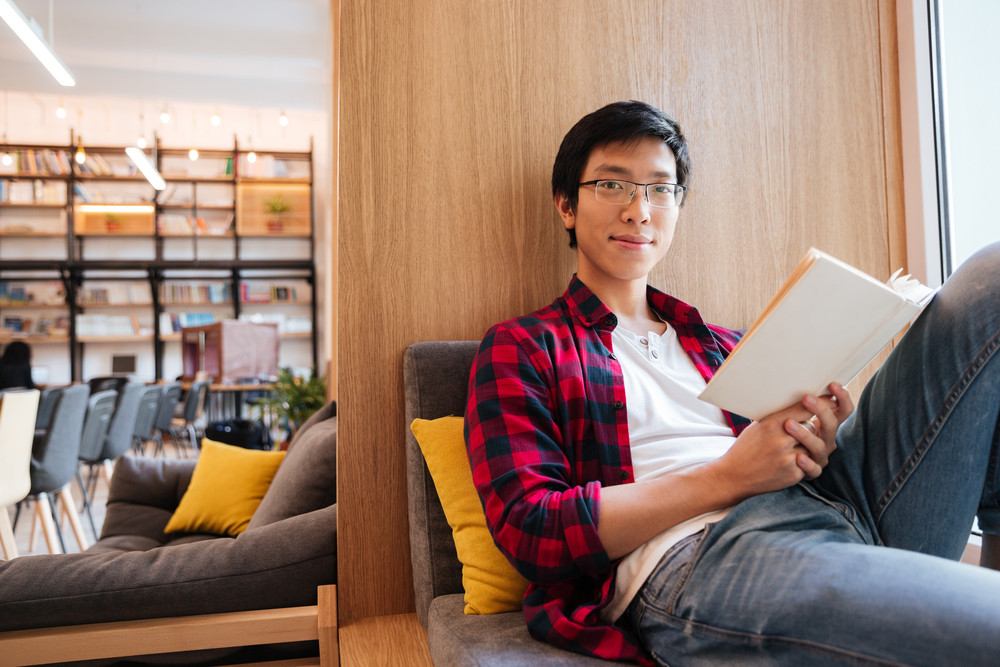 Image of happy asian student reading a book in university library sitting on sofa. Looking at camera.