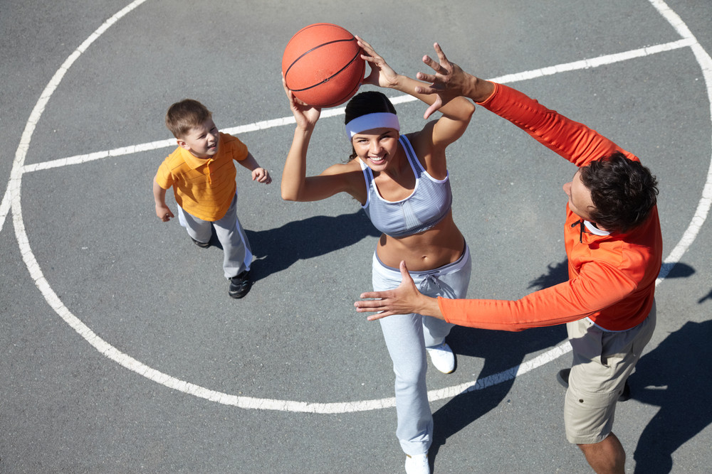 image of happy female going to throw ball into basket with man and