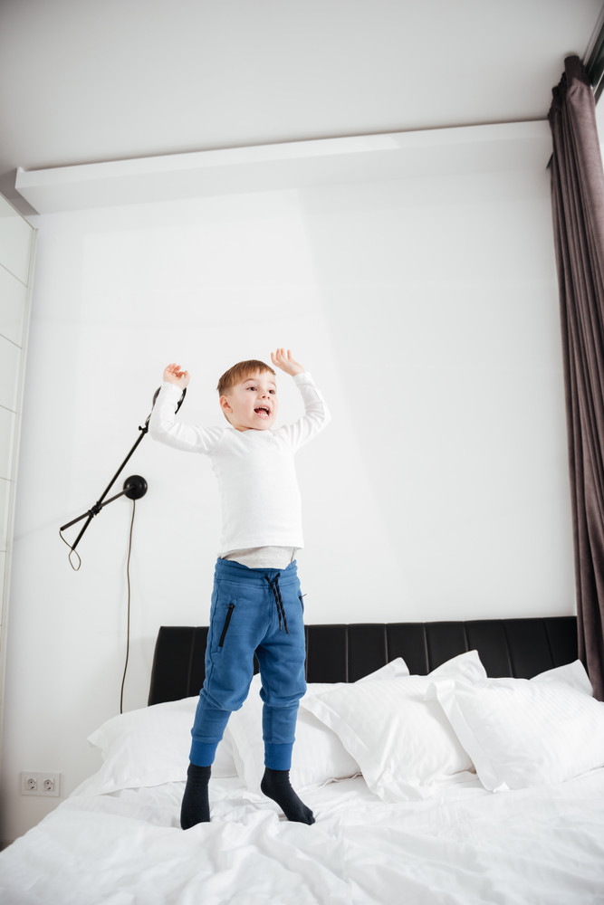 Image of happy little boy jumping on bed at home. Look aside.