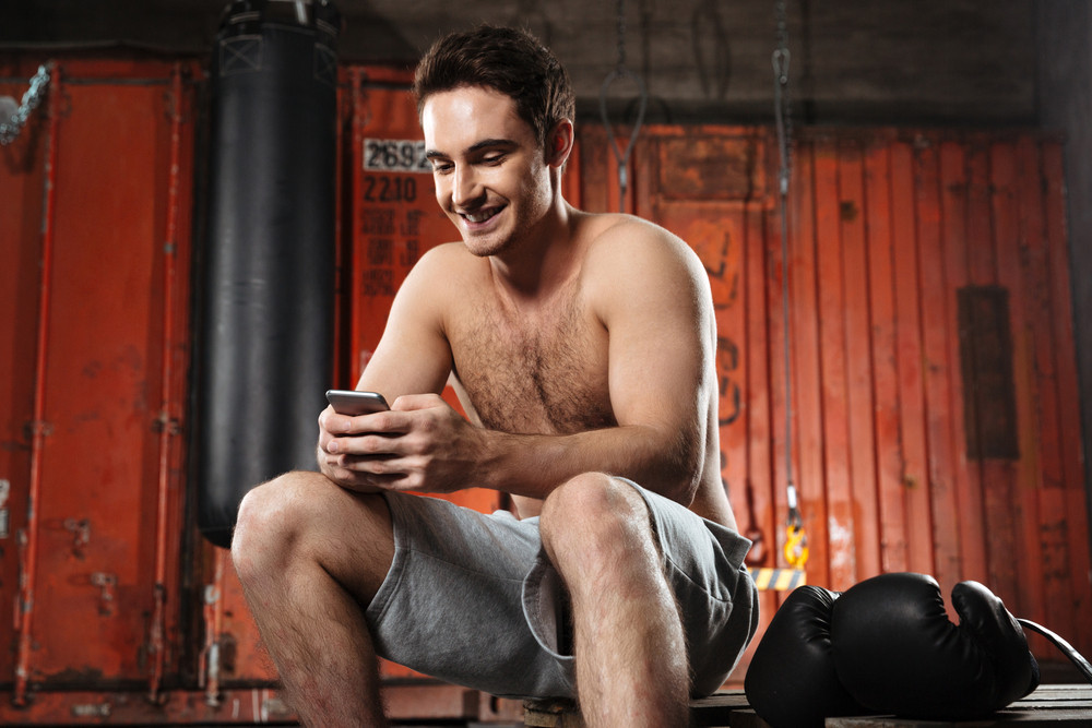 Image of happy man sitting in a gym while chatting by phone.