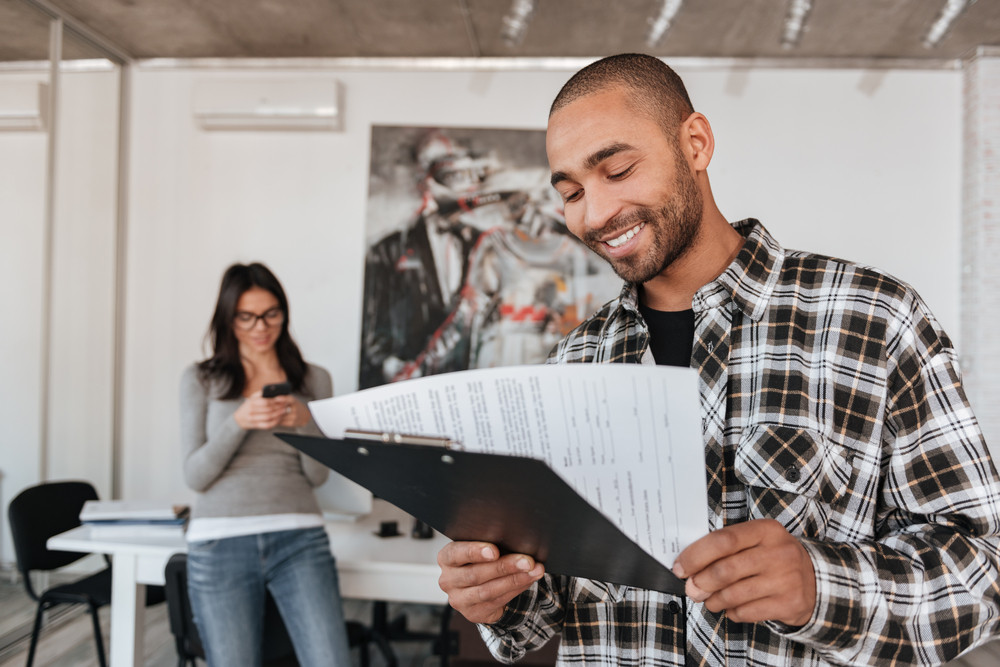 Image of happy young business partners indoors. African man holding clipboard. Focus on man.