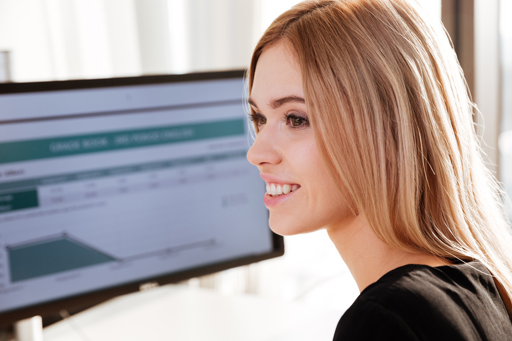 Image of happy young woman worker sitting in office near computer. Looking aside.