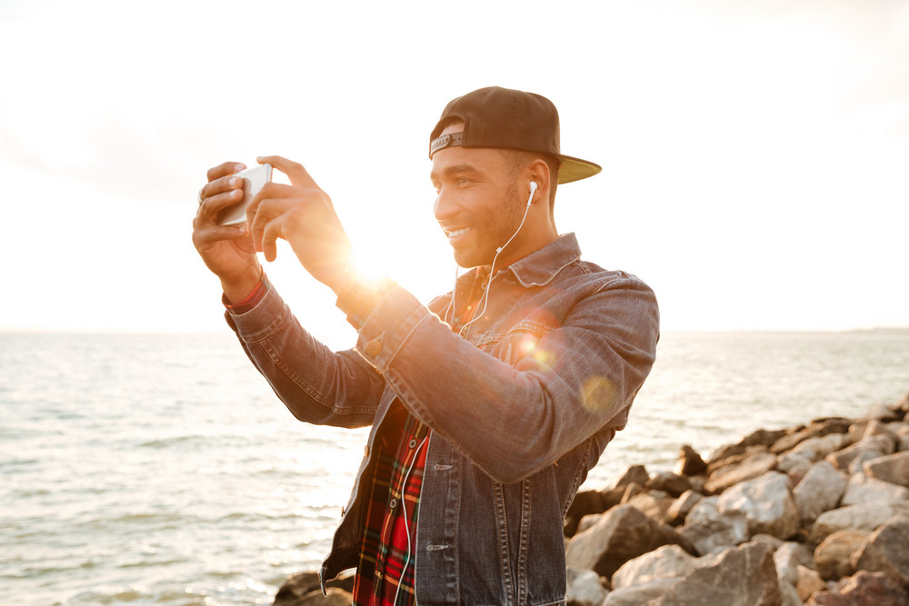 Image of joyful african man wearing cap walking on the beach while listening music with earphones. Take a photo of sea by phone.