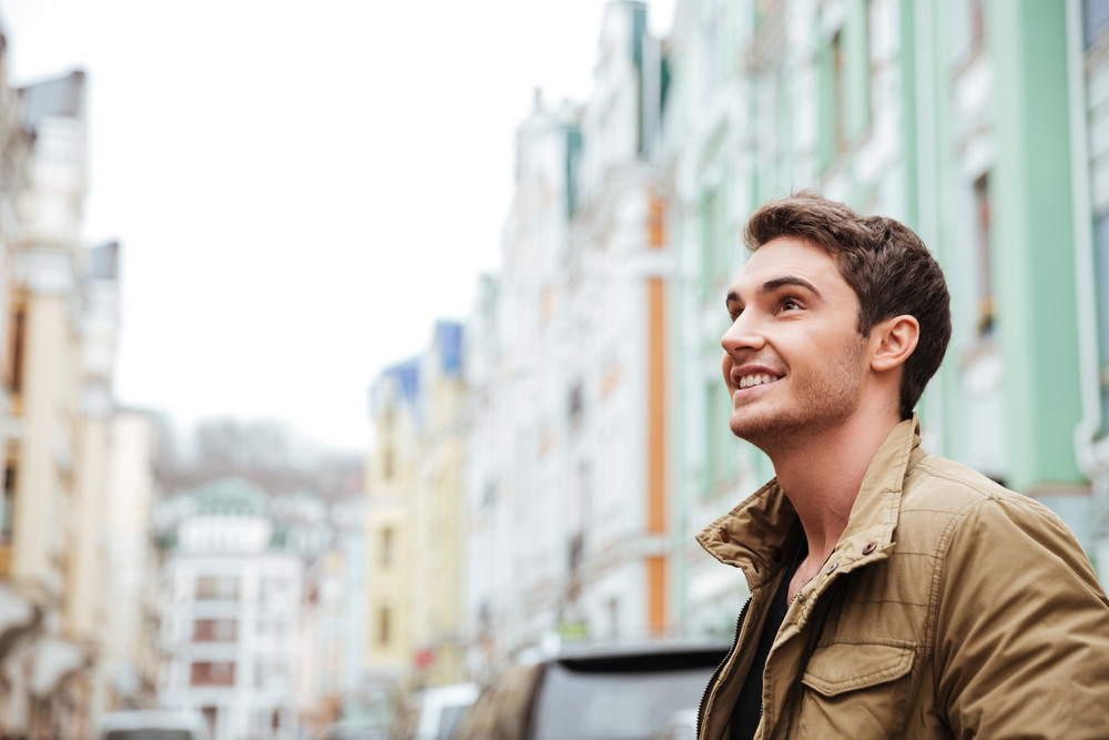 Image of joyful young man walking on the street and looking aside.