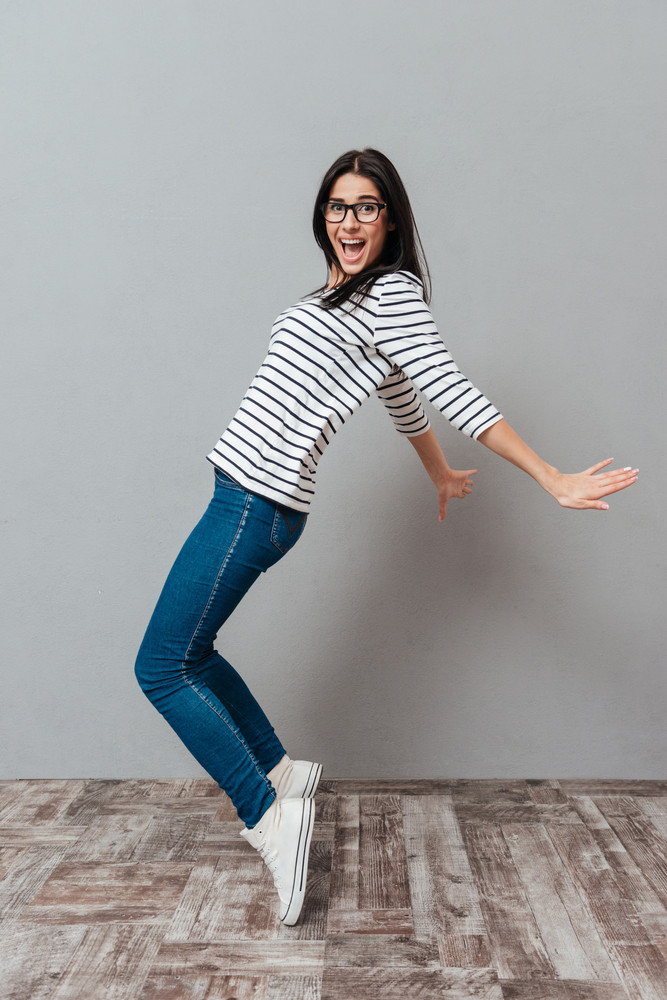 Image of joyful young woman wearing eyeglasses posing over grey background. Look at camera and screaming.