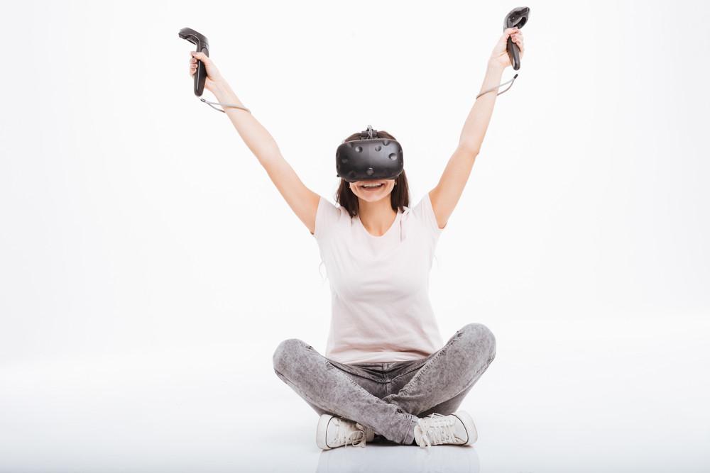 Image of joyful young woman wearing virtual reality device holding joysticks sitting over white background.