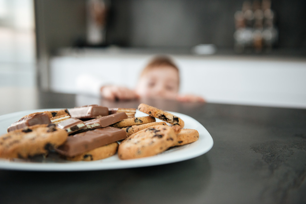 Image of little boy standing in kitchen while tries to eating cookies and chocolate. Focus on cookies.