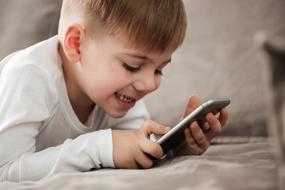 Image of little cheerful boy holding smartphone and playing game while sitting on sofa at home. Look at phone.