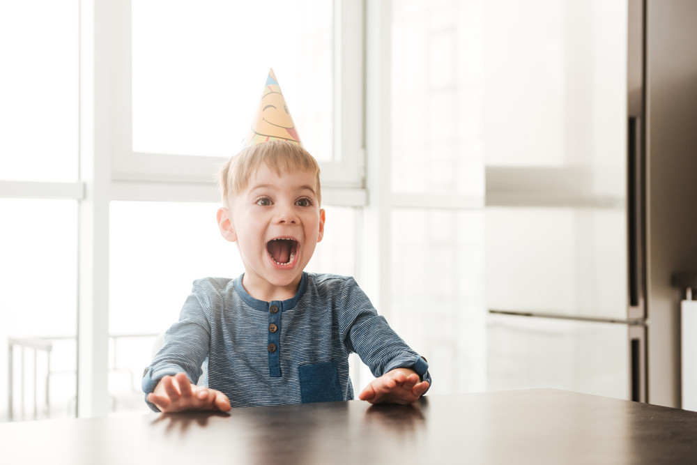 Image of little happy birthday boy sitting in kitchen while screaming. Look aside.