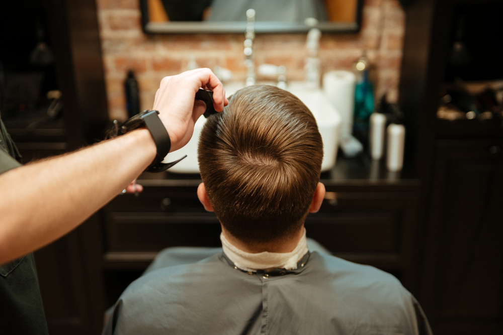 Image of man getting haircut by hairdresser with scissors while sitting in chair. Back view.