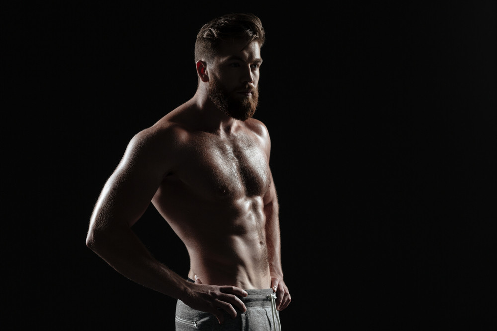 Image of naked athletic man. stands sideways. isolated dark background