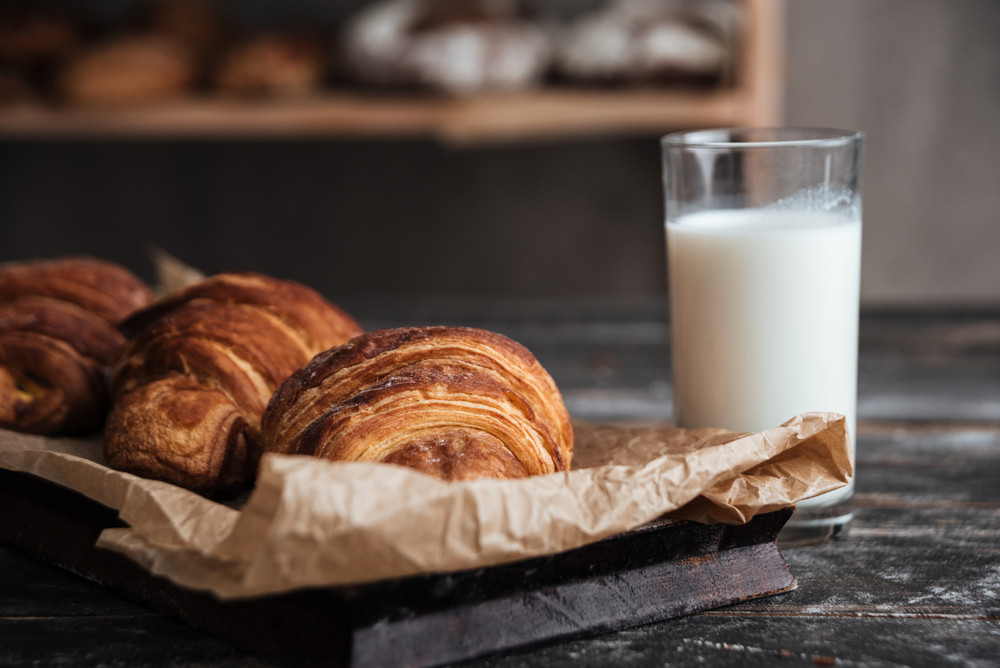 Image of pastries on dark wooden table background with milk at bakery