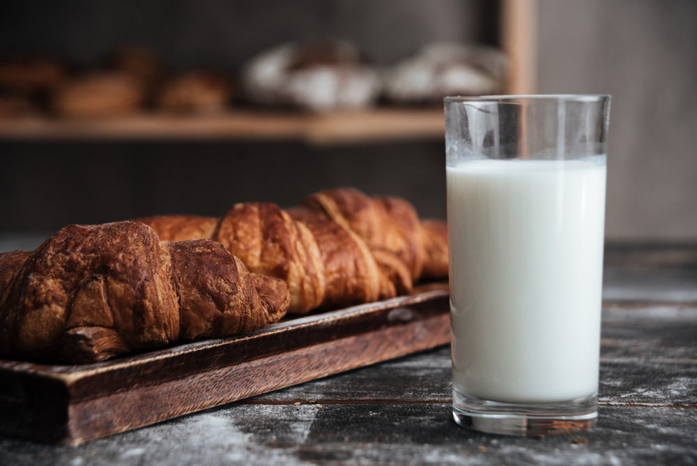 Image of pastries on dark wooden table on background with milk at bakery