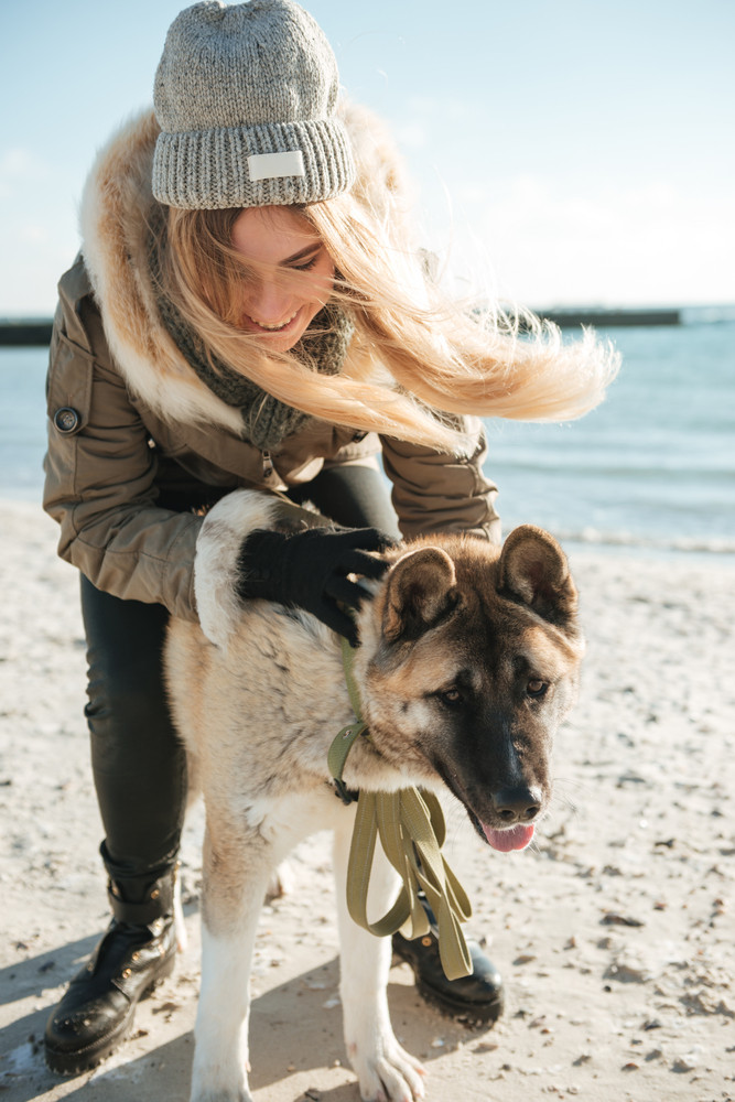 Image of playful young woman walks in winter beach with dog on a leash.