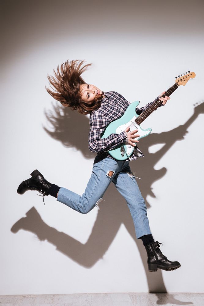 Image of pretty lady dressed in shirt in a cage holding guitar isolated over white background and jumping