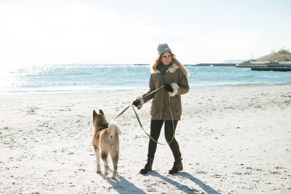 Image of pretty young girl walks in winter beach with dog on a leash.