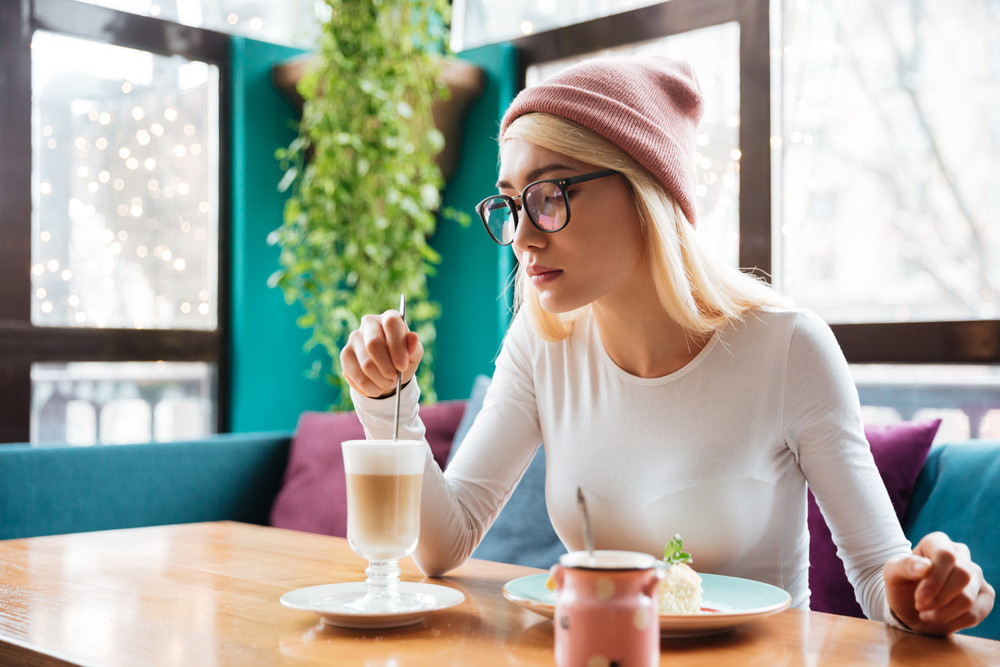 Image of pretty young lady wearing hat and glasses eating cake and drinking coffee while sitting in cafe.