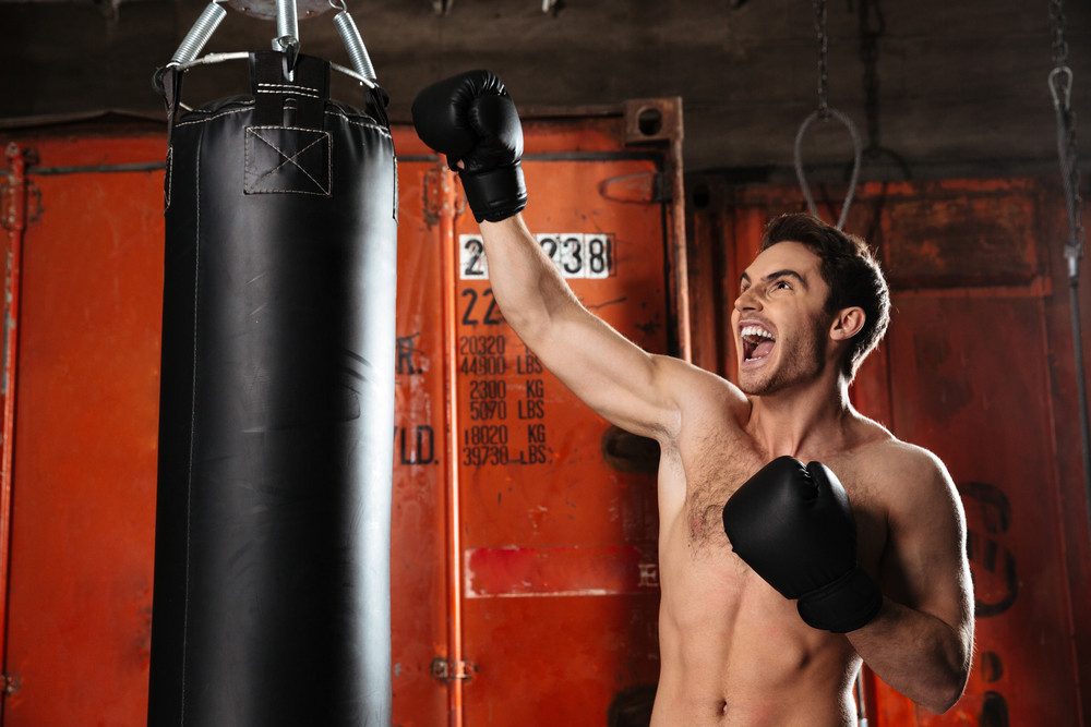 Image of screaming strong boxer training in a gym with punchbag. Looking aside.