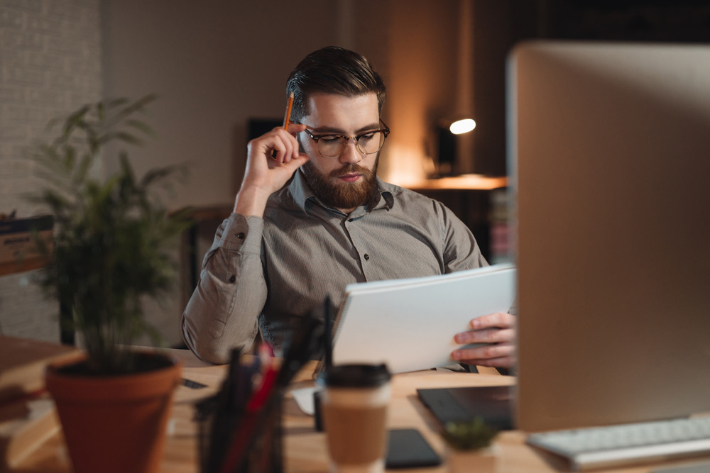 Image of serious bearded designer dressed in shirt working late at night with computer and drawing sketches in album.