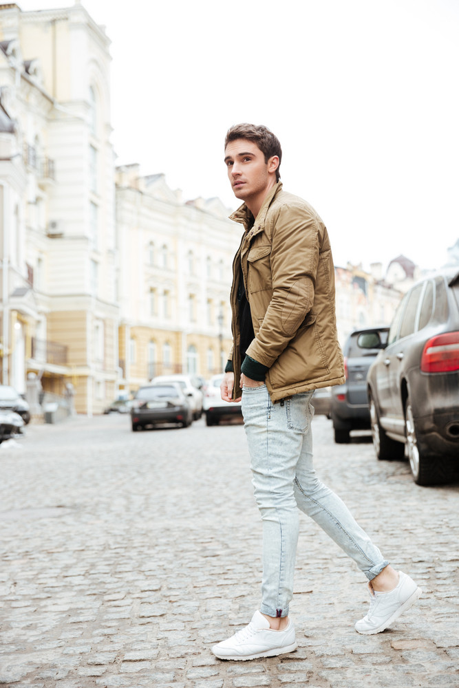 Image of serious young man walking on the street and looking aside.