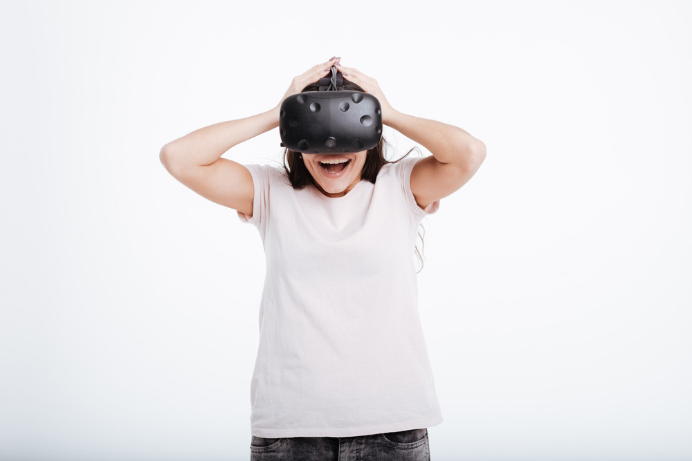 Image of shocked happy woman wearing virtual reality device over white background.