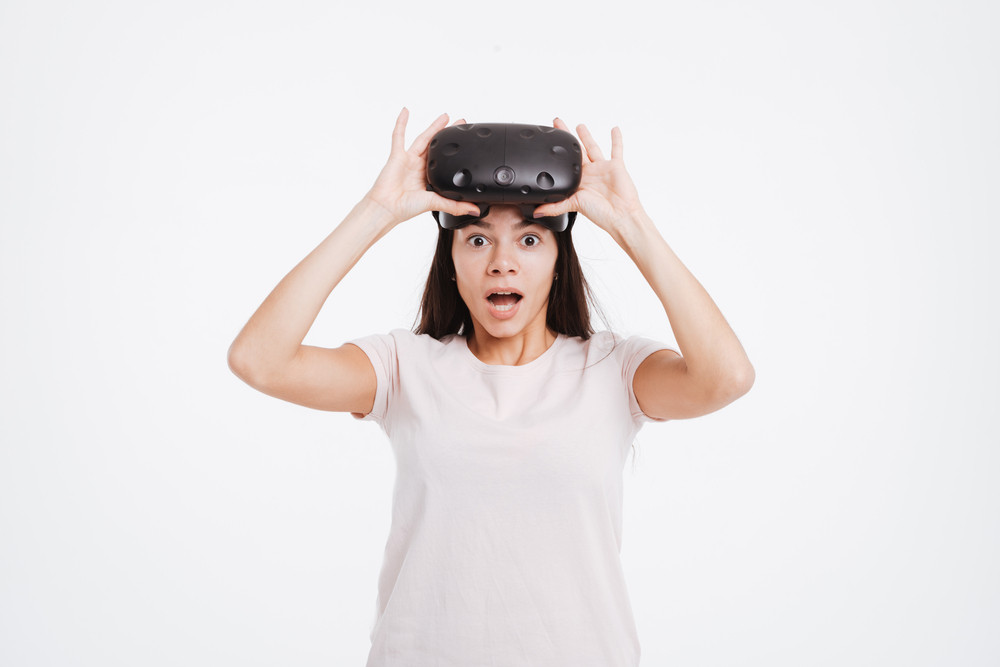 Image of shocked young woman wearing virtual reality device over white background.