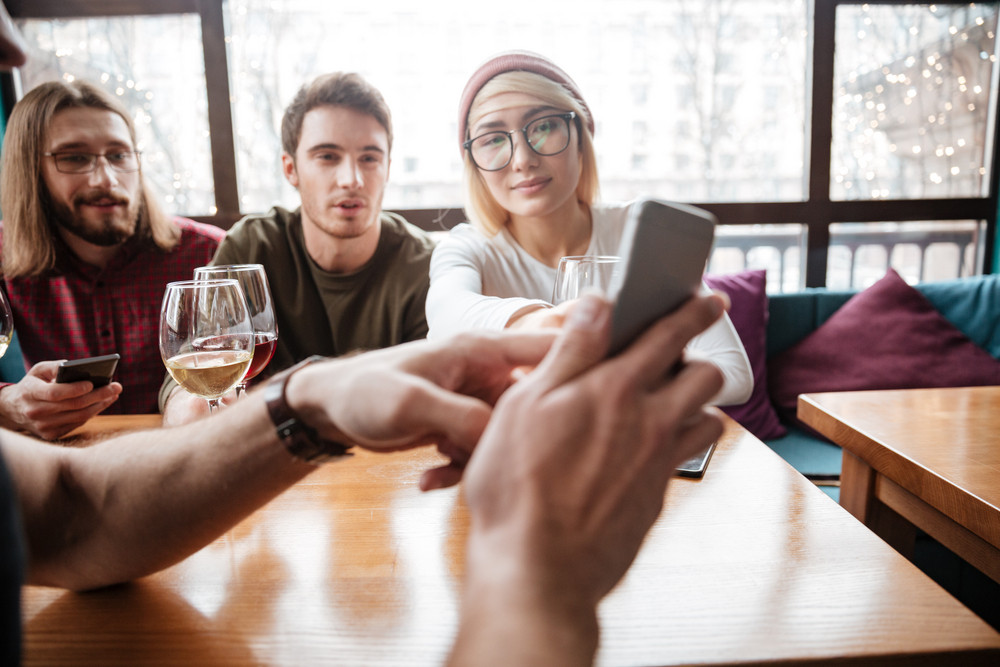 Image of smiling friends sitting in cafe and drinking alcohol and looking at phone.