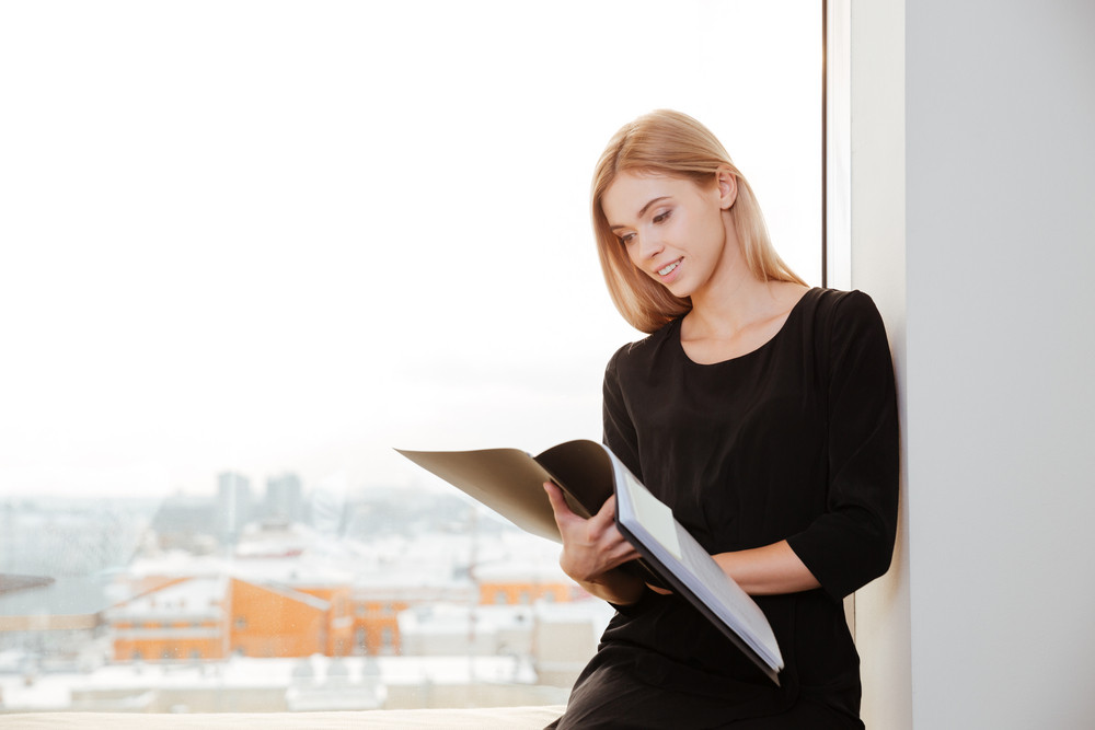 Image of smiling young lady worker standing in office holding folder.
